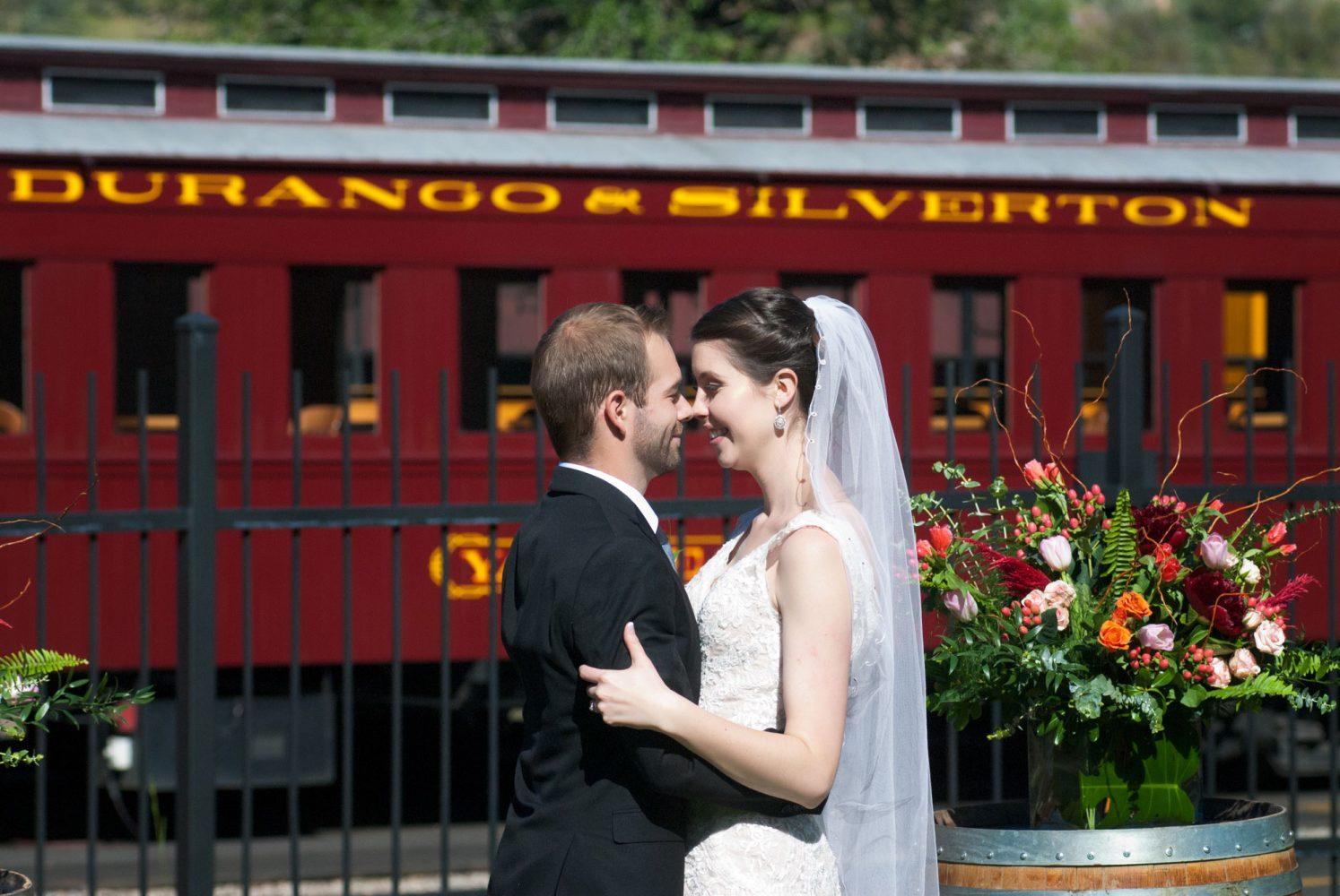 Happy bride + groom in front of the Durango & Silverton railroad car, Durango, Colorado