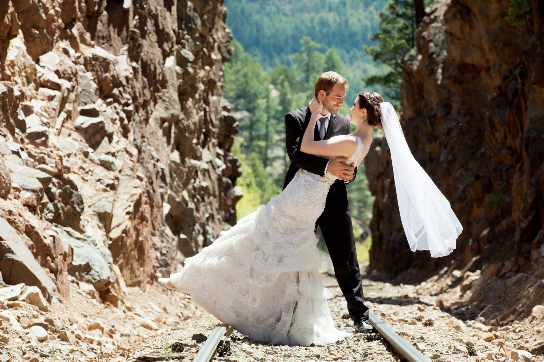 Happy bride + groom in on the railroad tracks in Cascade Canyon, Durango, Colorado