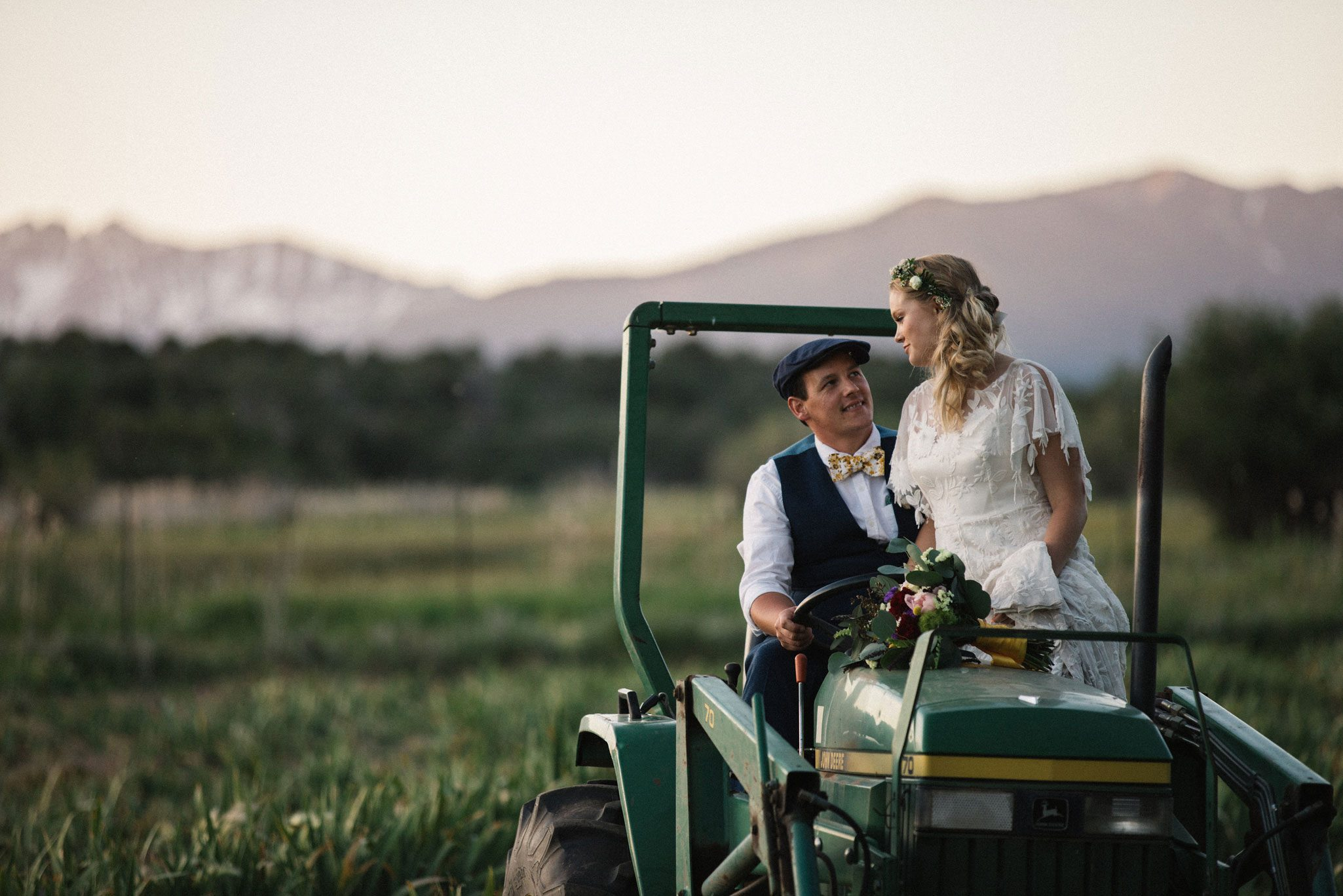 Bride & groom on a tractor at Ridgewood Event Center wedding, Durango, Colorado