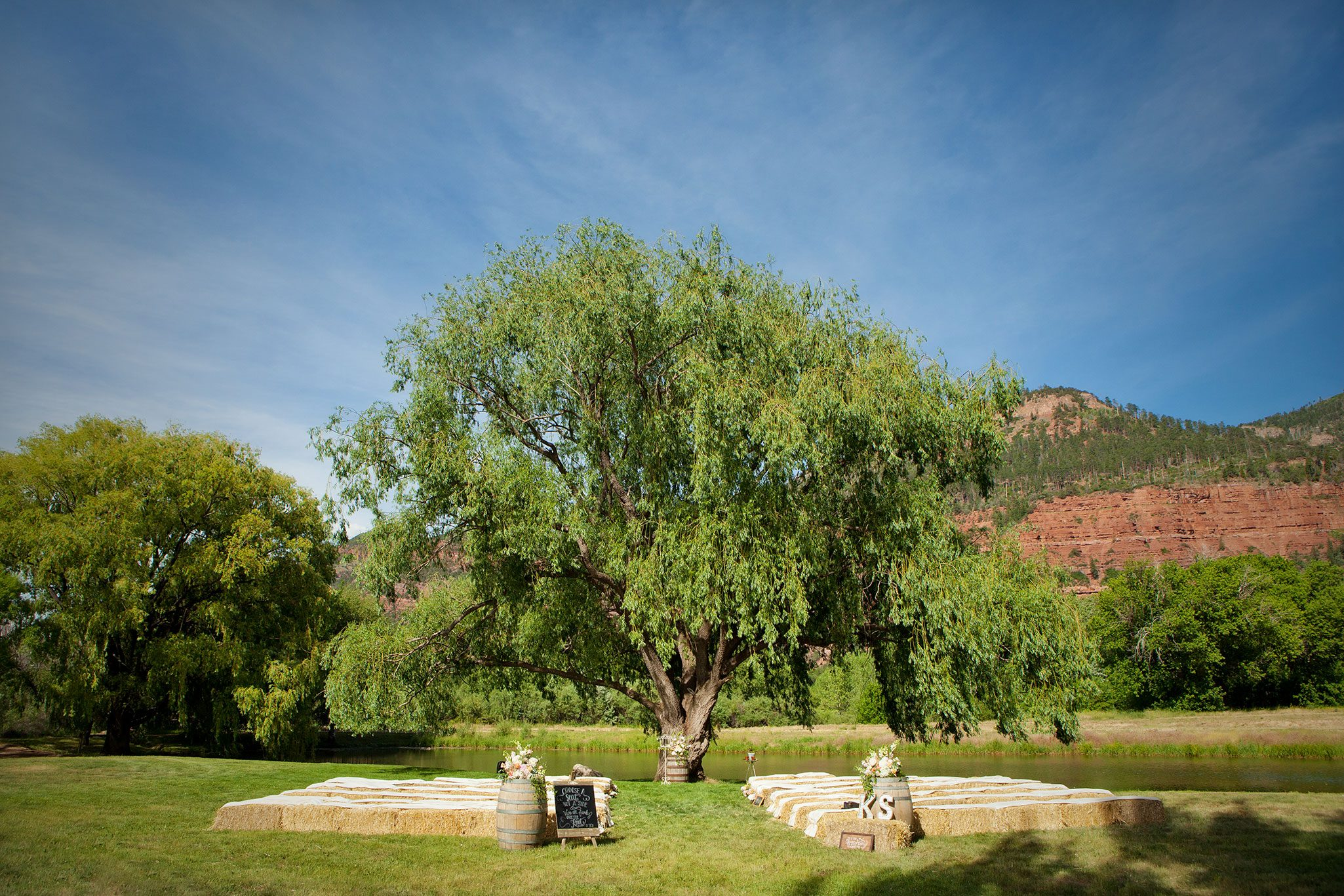 Ceremony on the pond under a huge willow tree with hay bale seating