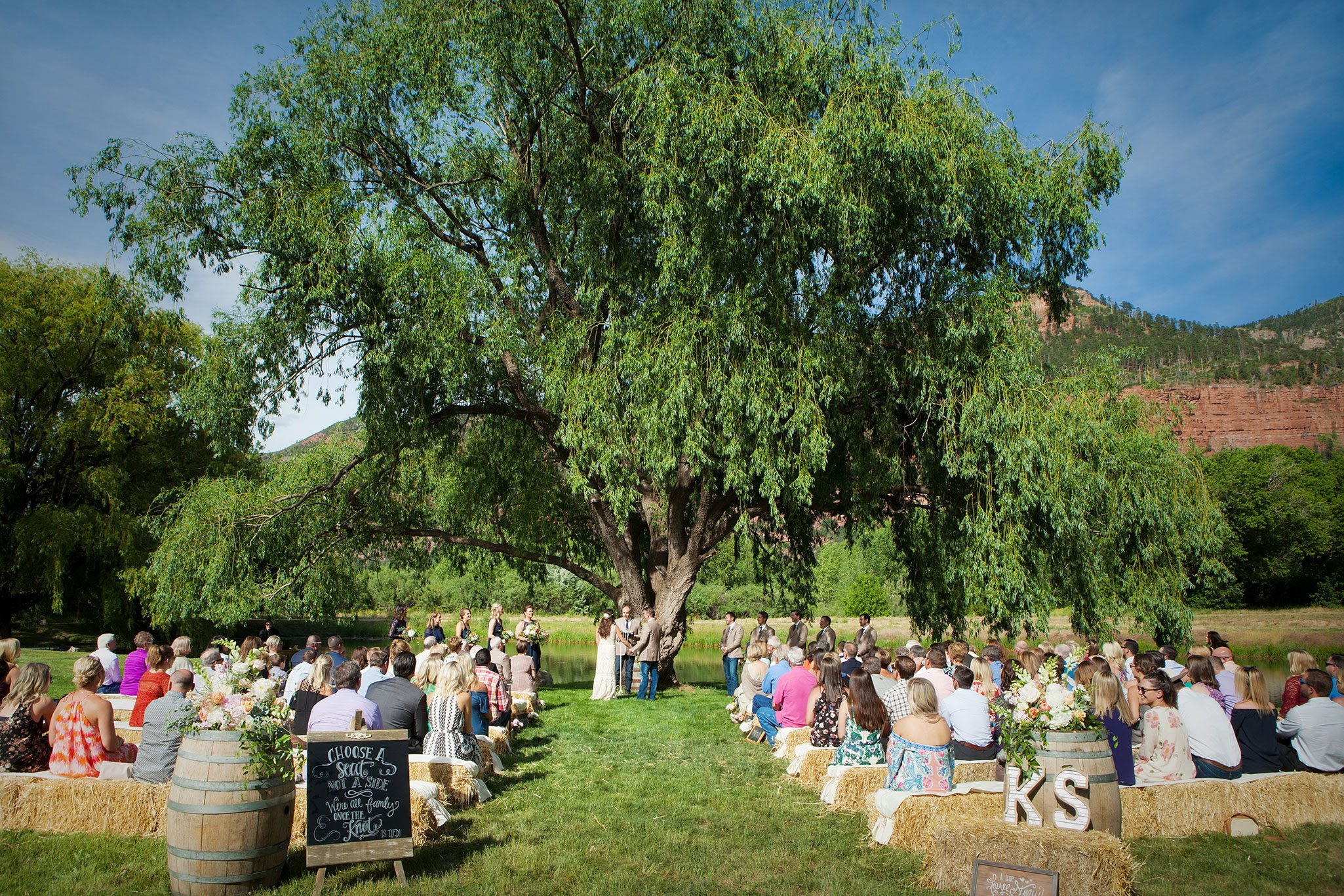 wedding ceremony under a willow tree with hay bale seating