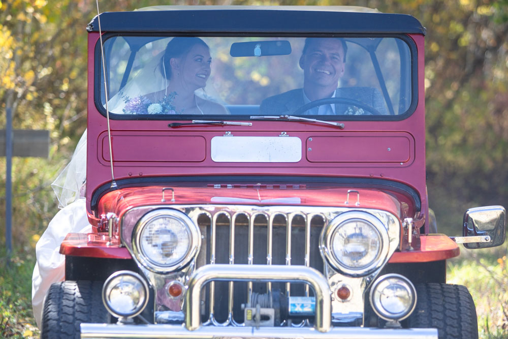 Bride arriving to ceremony in a red 1951 Willys jeep