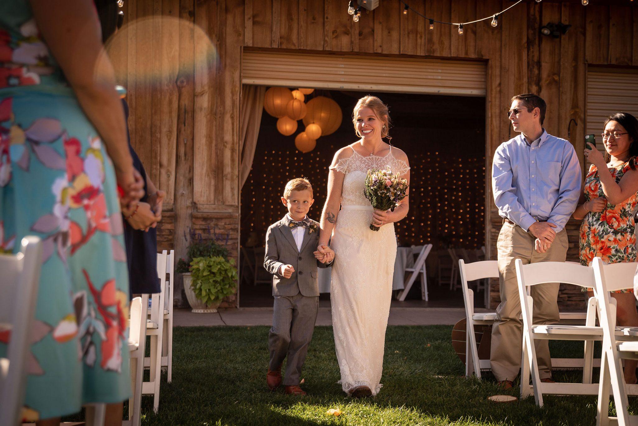 Bride and son walking down the aisle   Durango Weddings Magazine