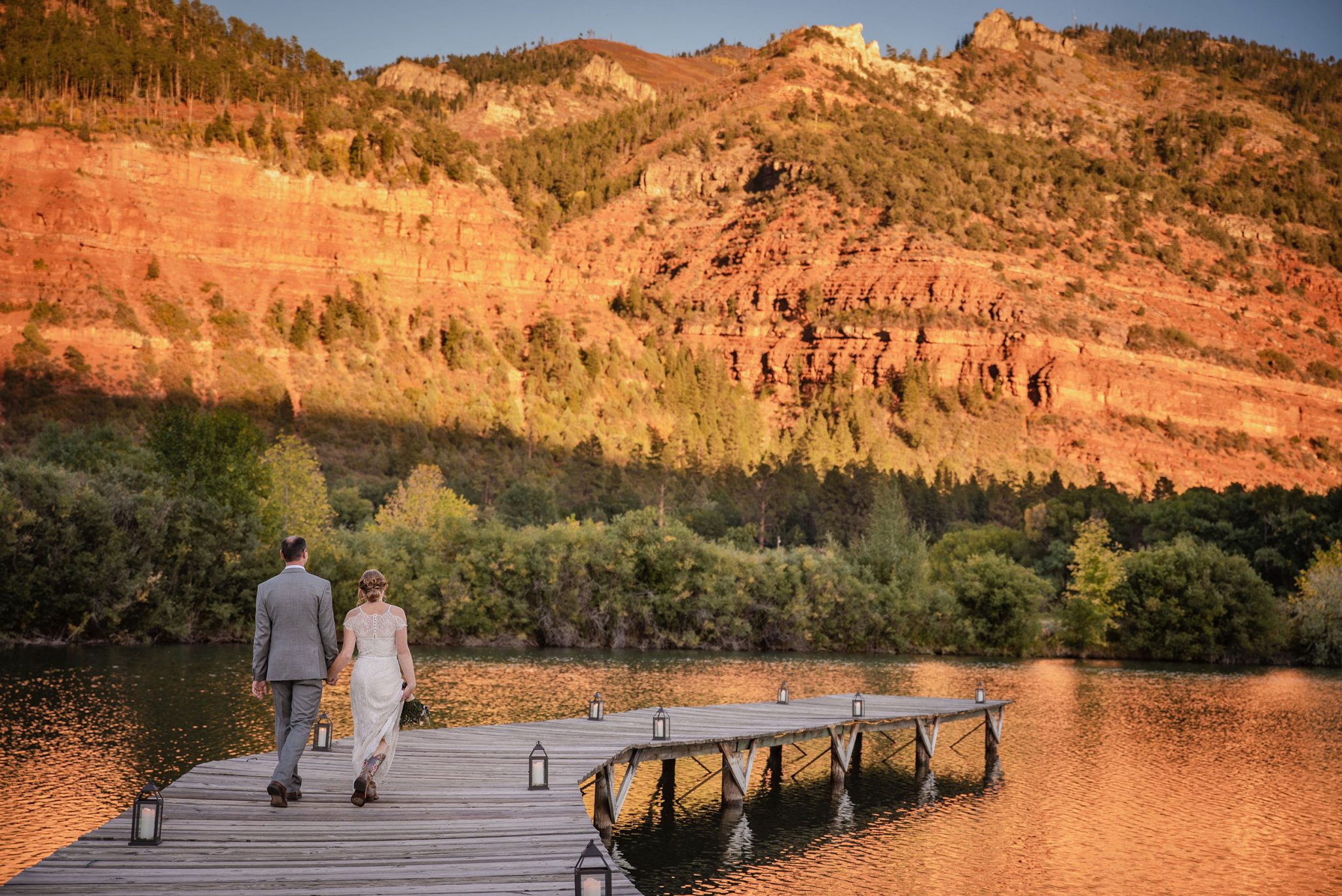 Bride & Grrom walking down the dock at River Bend Ranch | Durango Weddings Magazine
