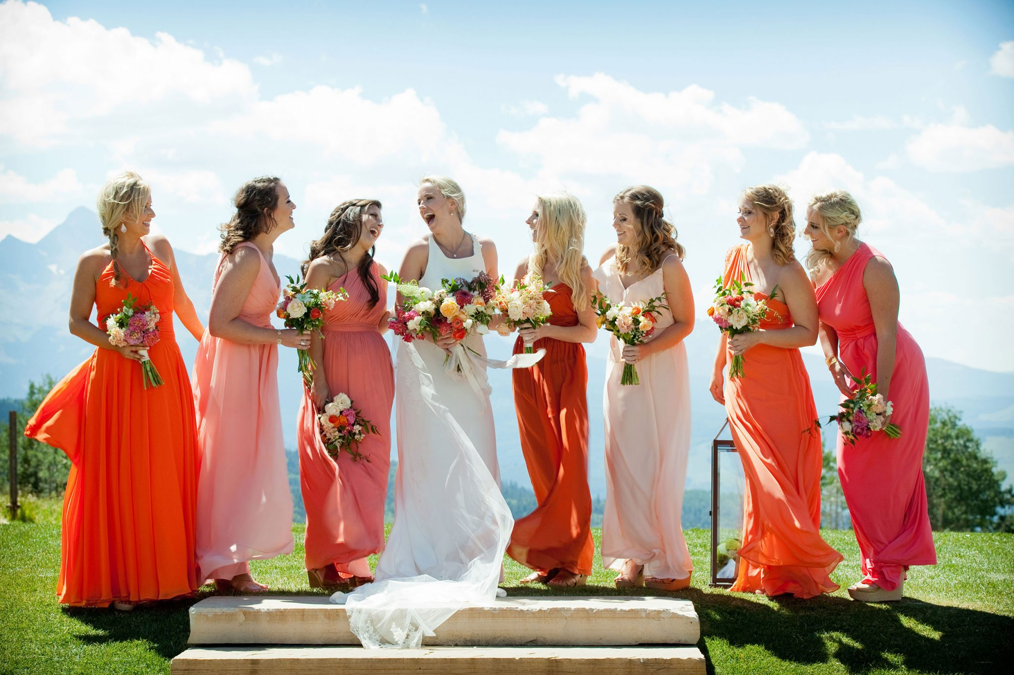 Bridesmaids dressed in the clolors of the alpineglow sunset including Pantone's 2019 Color of the Year: Living Coral