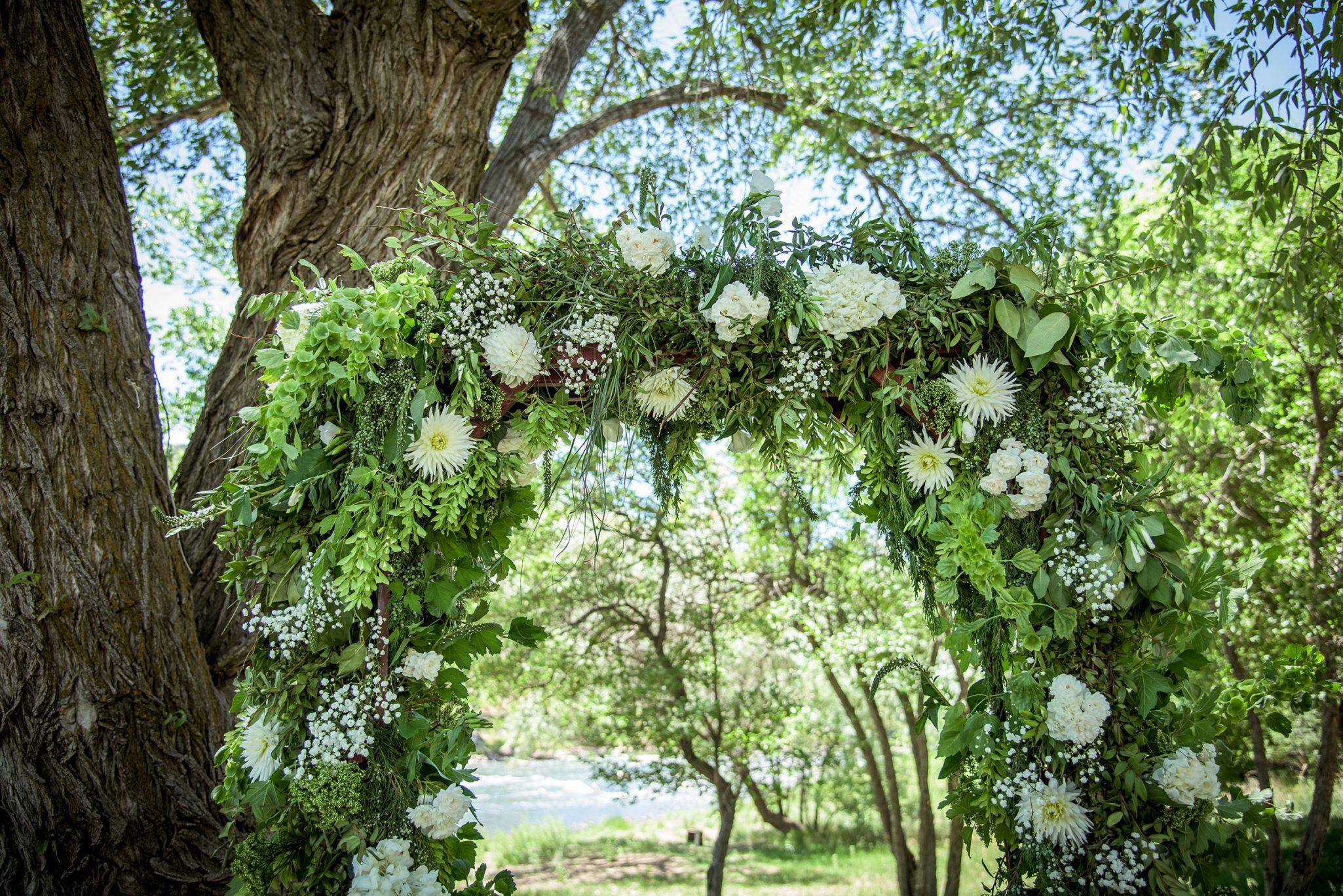 Floral filled ceremony arch along with Animas River via Durango Weddings Magazine
