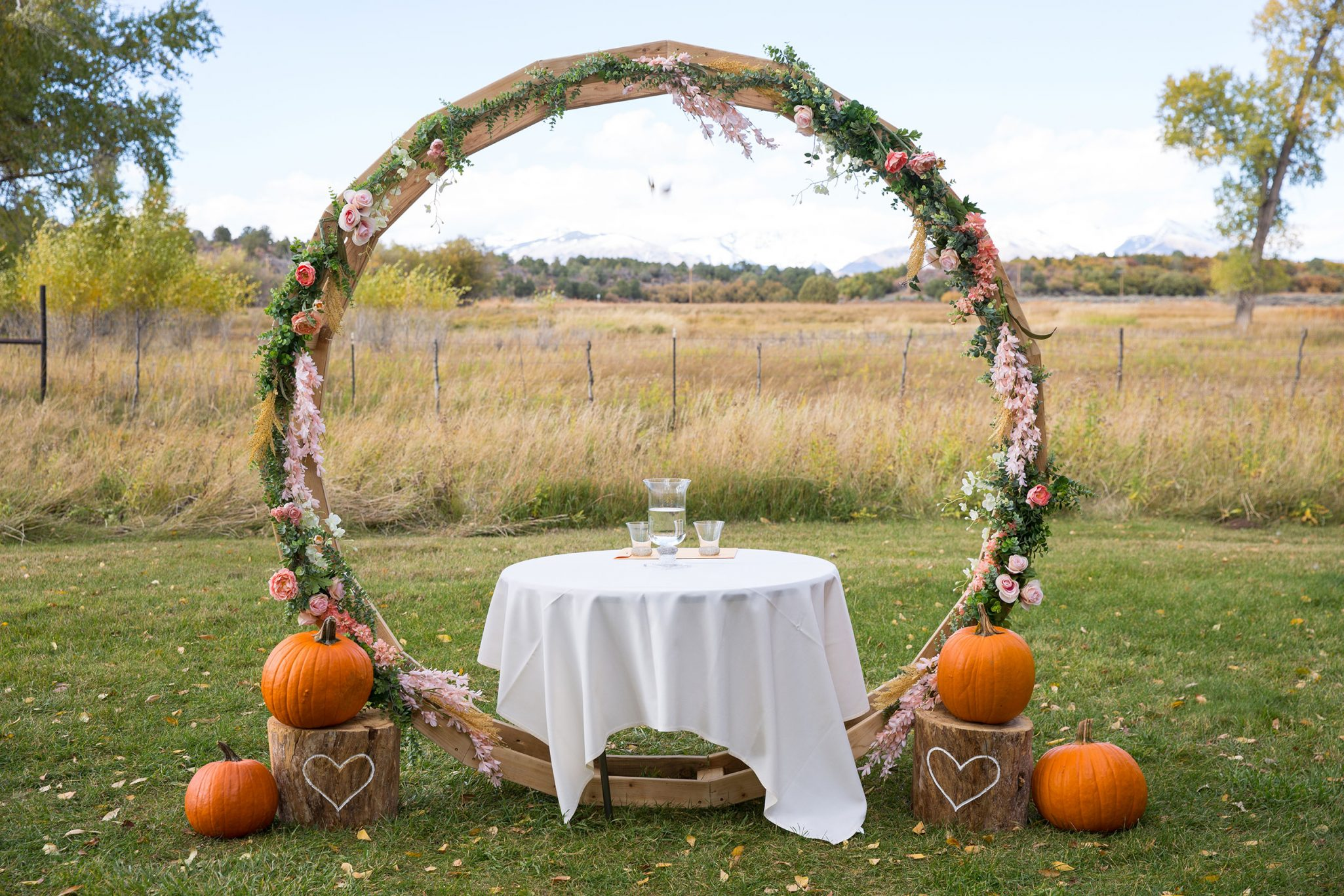 Ceremony arch with rose and pumpkin decor