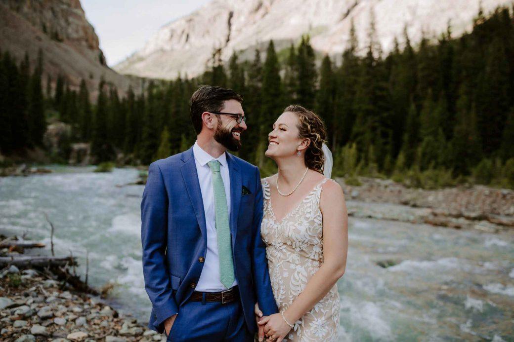Happy bride & groom along the river